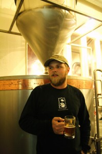 Brewer Chris Miller leans on hopback at Snipes Mountain Brewery