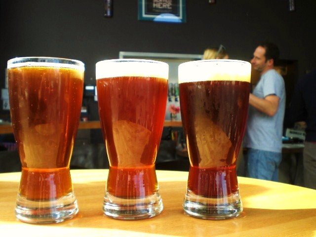 (l to r) Ninkasi Quantum Pale Ale, Irish Red, and Believer Imperial Red