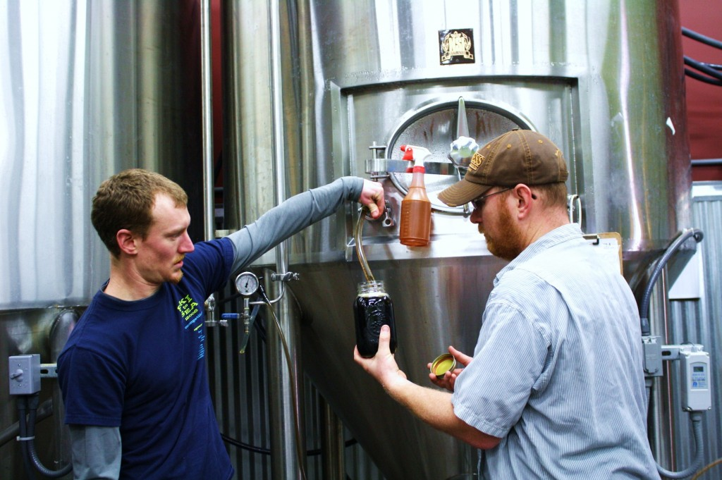 Oakshire brewer Joe Jasper (left) and founder Jeff Althouse pull O'Dark :30 from tank.