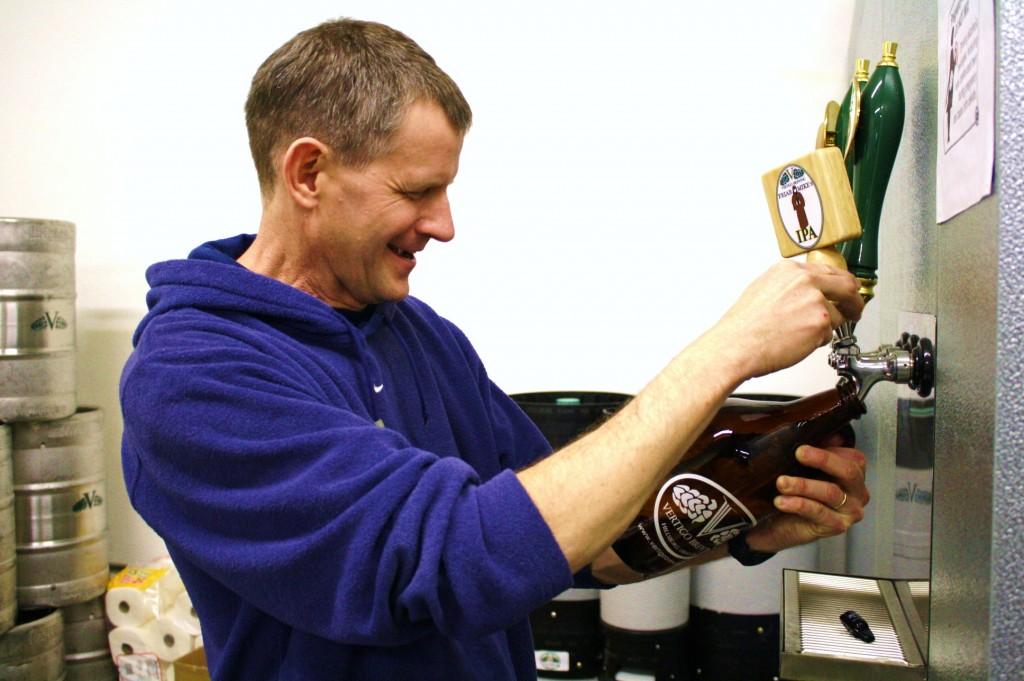 Vertigo Brewing co-founder and brewer Mike Haines pours an inaugural growler of Friar Mike's IPA