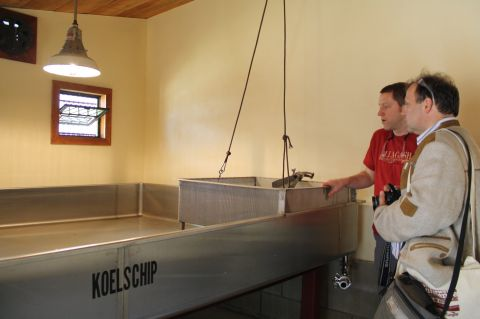 Allagash brewmaster Jason Perkins (red shirt) shows the Koelschip room to Cornelius Faus,t founder of Faust Brewing of Miltenberg, Germany.