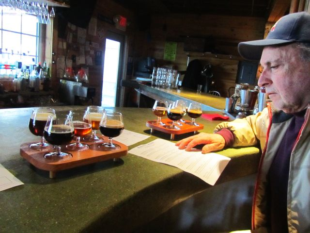 Mick De Ieso inspects the tap list and samples at Marshall Wharf Brewery in Belfast, Maine