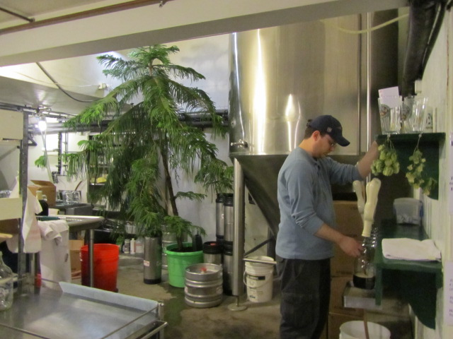 Adam Chandler pours beer at Oak Pond Brewery