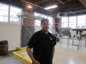 Fort George co-founder Chris Nemlowill by canning line at new brewery