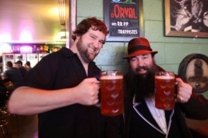 Brothers Tim (left) and Chris Ensign toast mugs of Fort George Vortex for their birthdays at APEX