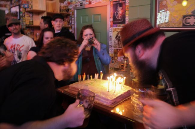 Tim (left) and Chris Ensign blow out the candles on their birthday cake at APEX