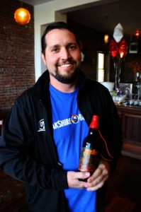 Oakshire Brewmaster Matt Van Wyk with a bottle of Hellshire I Bourbon Barrel-aged Barleywine
