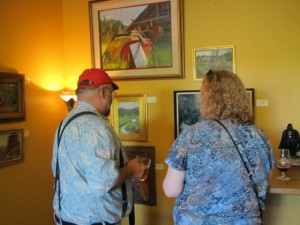 John Foyston (left) and Lisa Morrison check out some of Foyston's paintings at The BeerMongers