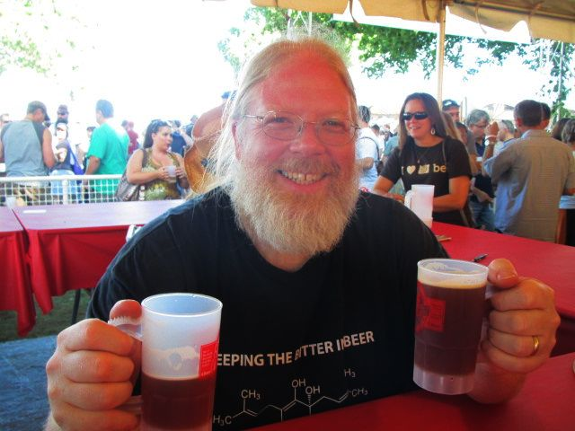 Full Sail Brewmaster John Harris in the Oregon Brewers Festival Buzz Tent with mugs of his 1995 Old Boardhead Barleywine