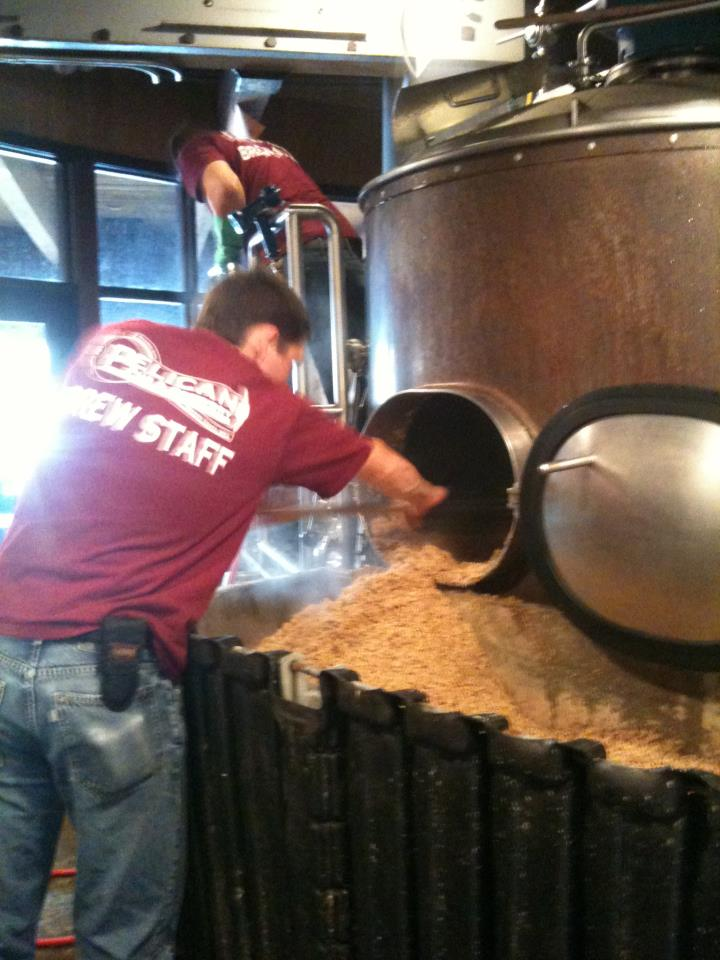 Pelican brew staff emptying grain from tank while brewing Silverspot IPA (photo from Pelican)
