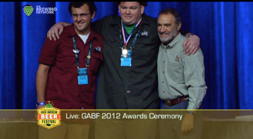 Harvester brewers John Dugan (left) and James Neumeister (center) win a bronze medal for their gluten-free Pale Ale at the 2012 GABF. Charlie Papazian of the Brewers Association on the far right.