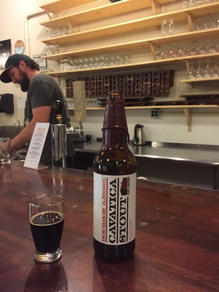 Taylor Jensen pops a bottle of Fort George Cavatica (bbl aged) at N.W.I.P.A/