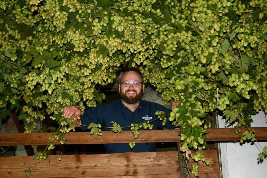 Laurelwood's Shane Watterson surrounded by his favorite plant (photo courtesy of Laurelwood Brewing)