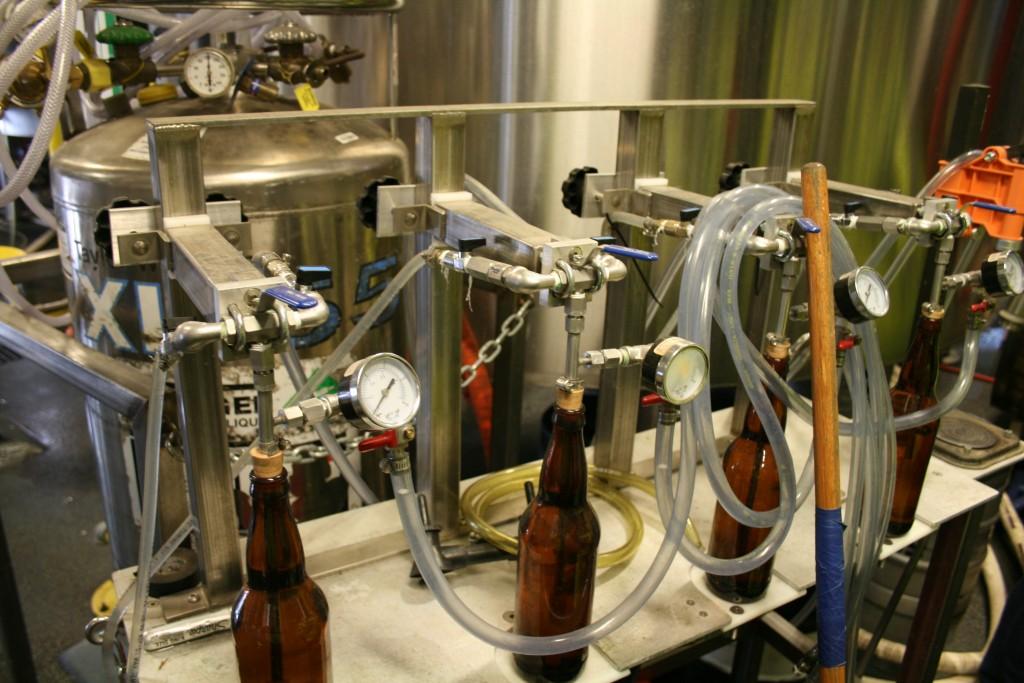 Hand bottle filler at 10 Barrel Brewing