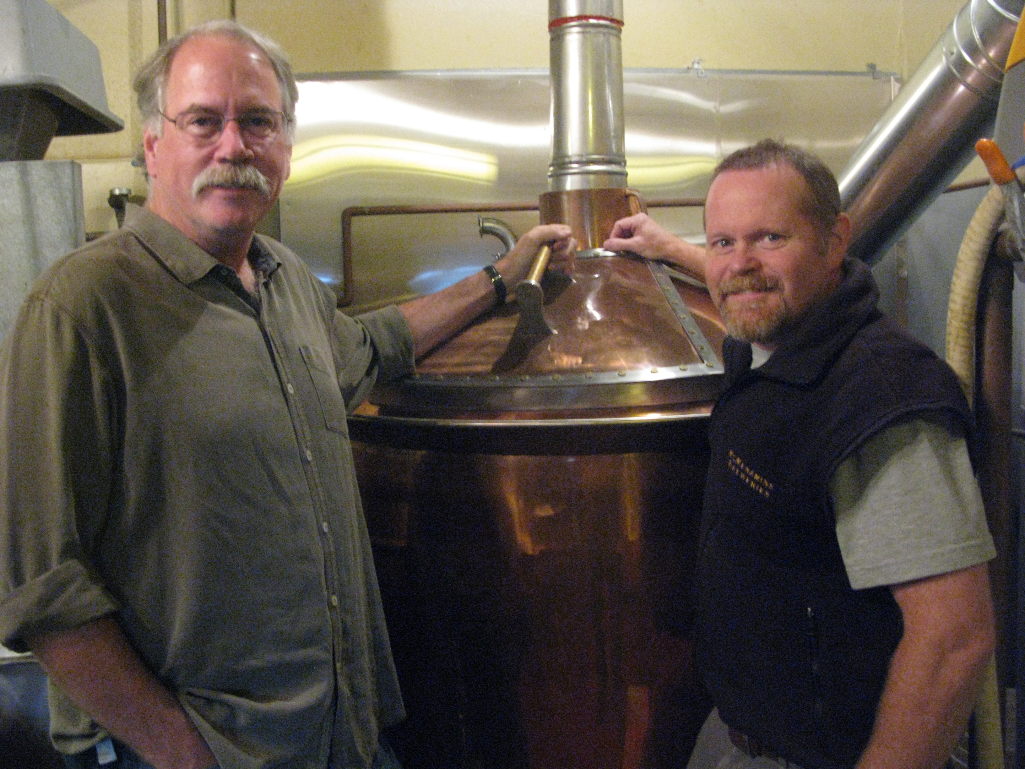 "Brian McMenamin and brewery general manager Rob Vallance in the Hillsdale Pub brewery with the new copper kettle (master Portland metalsmith Curtis Patience made the copper dome for the new kettle.) When the McMenamins first built the brewery -- Captain Neon's FGermentation Chamber -- they found a Portland company to build them a copper brew kettle, but it was an idiosyncratic piece of work, Vallance says, because nobody -- niether brewers nor fabricators -- knew what small brewers really needed. For year, craft breweries were cobbled together with old dairy and kitchen equipment and even tanks from the mothballed WPPSS nuclear power plant. Modern craft brewers have an easier time of it today, with great craftsmen and fabricators such as JV Northwest, Metalcraft, Portland Kettle Works, Practical Fusion and more catering to their needs. also bad pic of first brewsheet and Jeff Cooley "" Jeff Cooley, who formulated the recipe for the reborn Hillsdale Ale, which clocks in at 38 IBU and 4.5 percent ABV. He was a brewer before he became a brewery district manager and yes, you could safely say that he likes his hops..."
