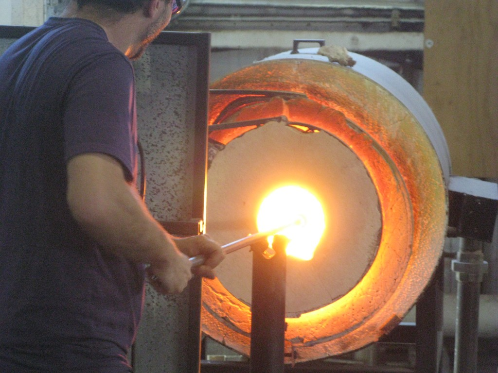 Glassblower and shop foreman Aaron Frankel reheats a nascent Oregon Pint to prevent it from cooling too much during shaping. FoystonFoto