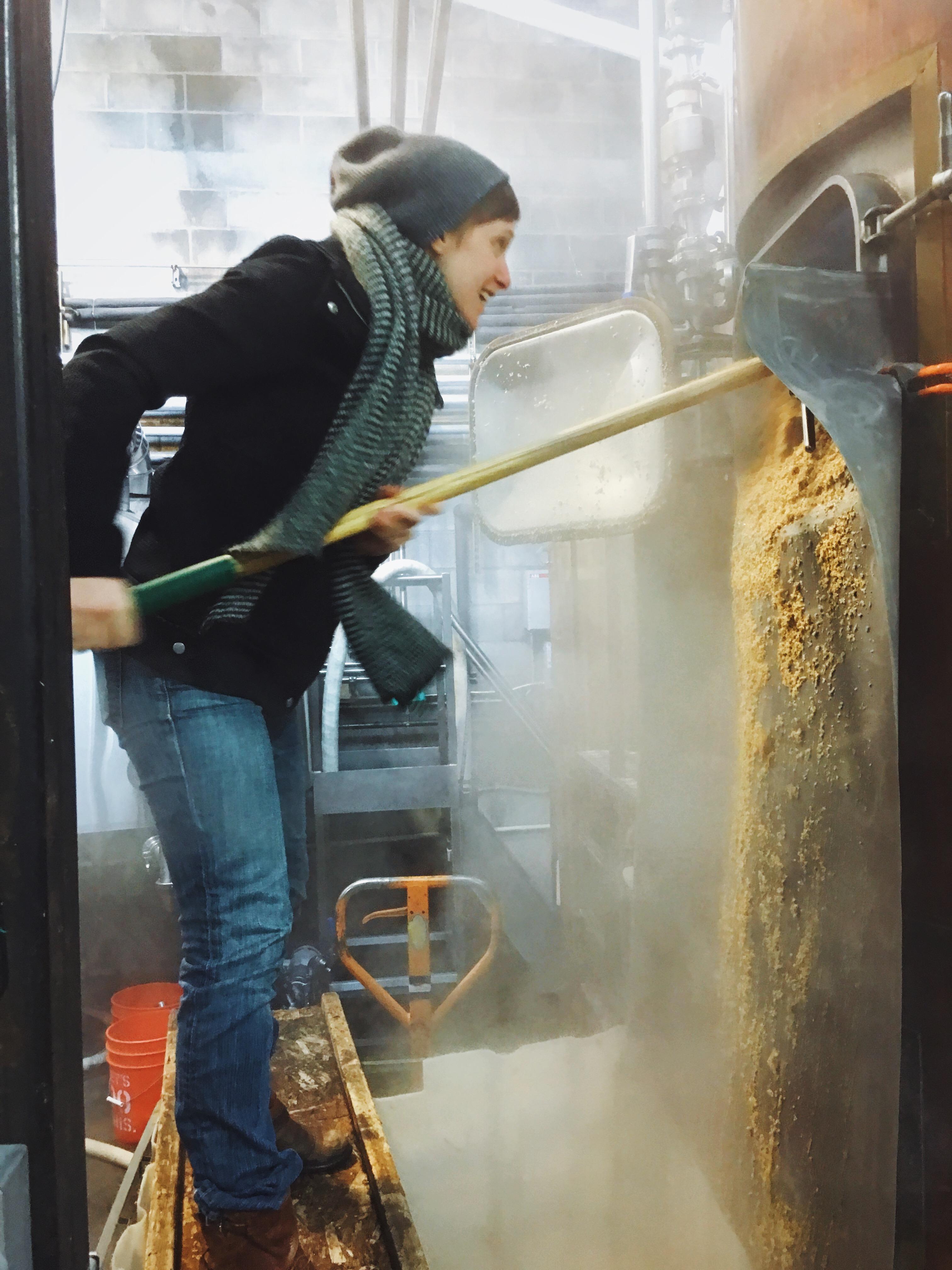 Eve shoveling grain. (image courtesy of Everybody's Brewing)