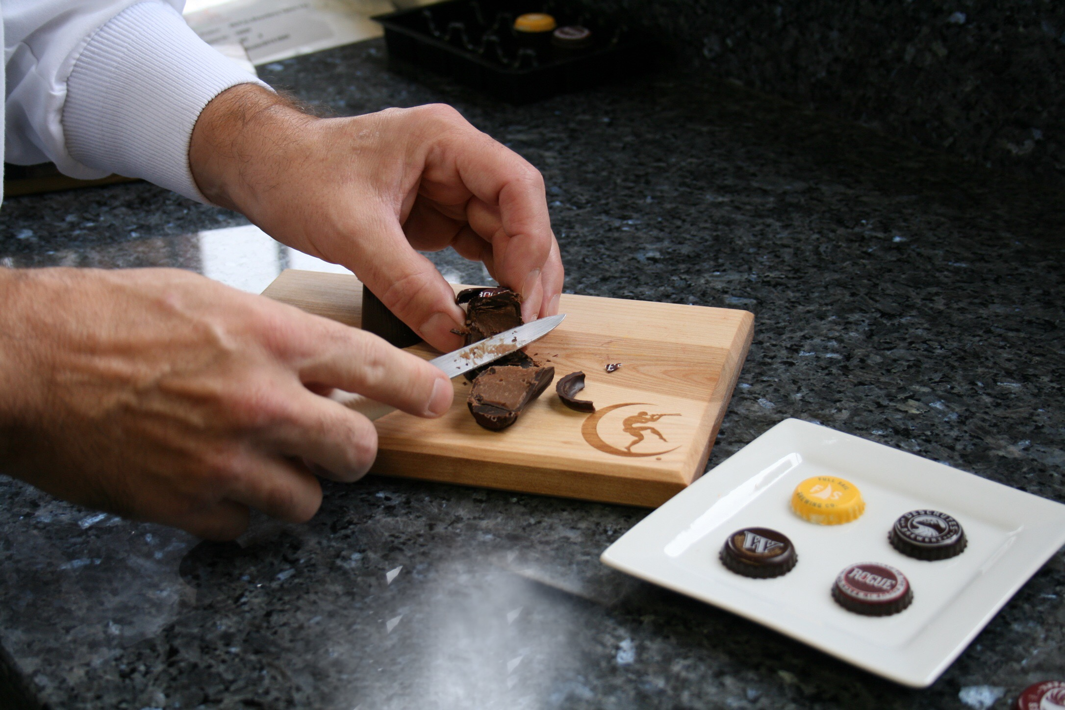 Julian Rose cutting a Moonstruck Chocolate Oregon Craft Brewers Collection Rogue Truffle. (photo by D.J. Paul)