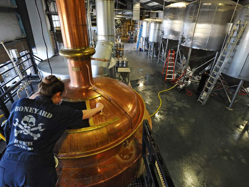 Boneyard brewer Dana Robles looks into the well used copper kettle. (photo courtesy of Andy Tullis)