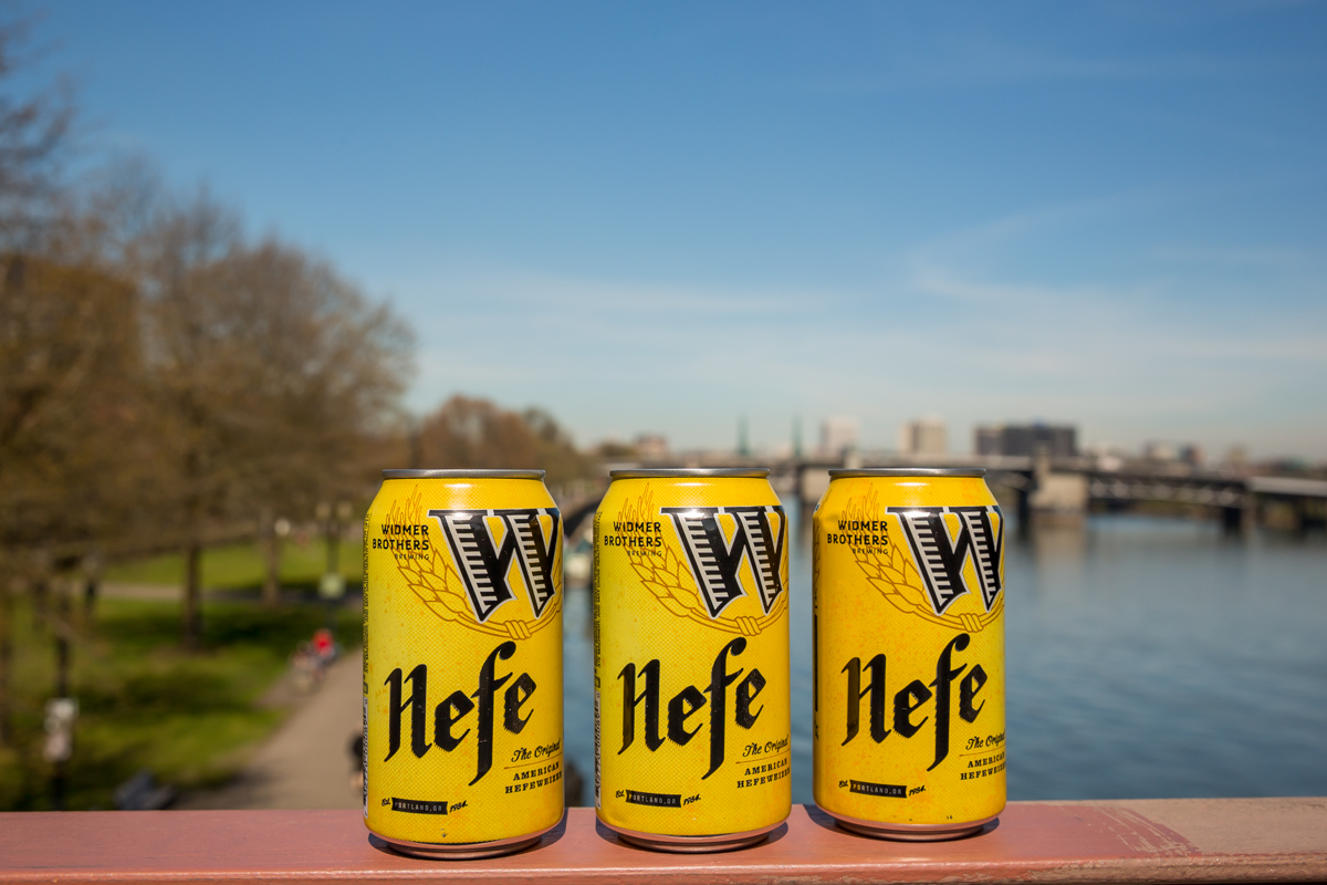 Cans of Widmer Brothers Brewing Hefe above the Willamette River. (image courtesy of Widmer Brothers Brewing)
