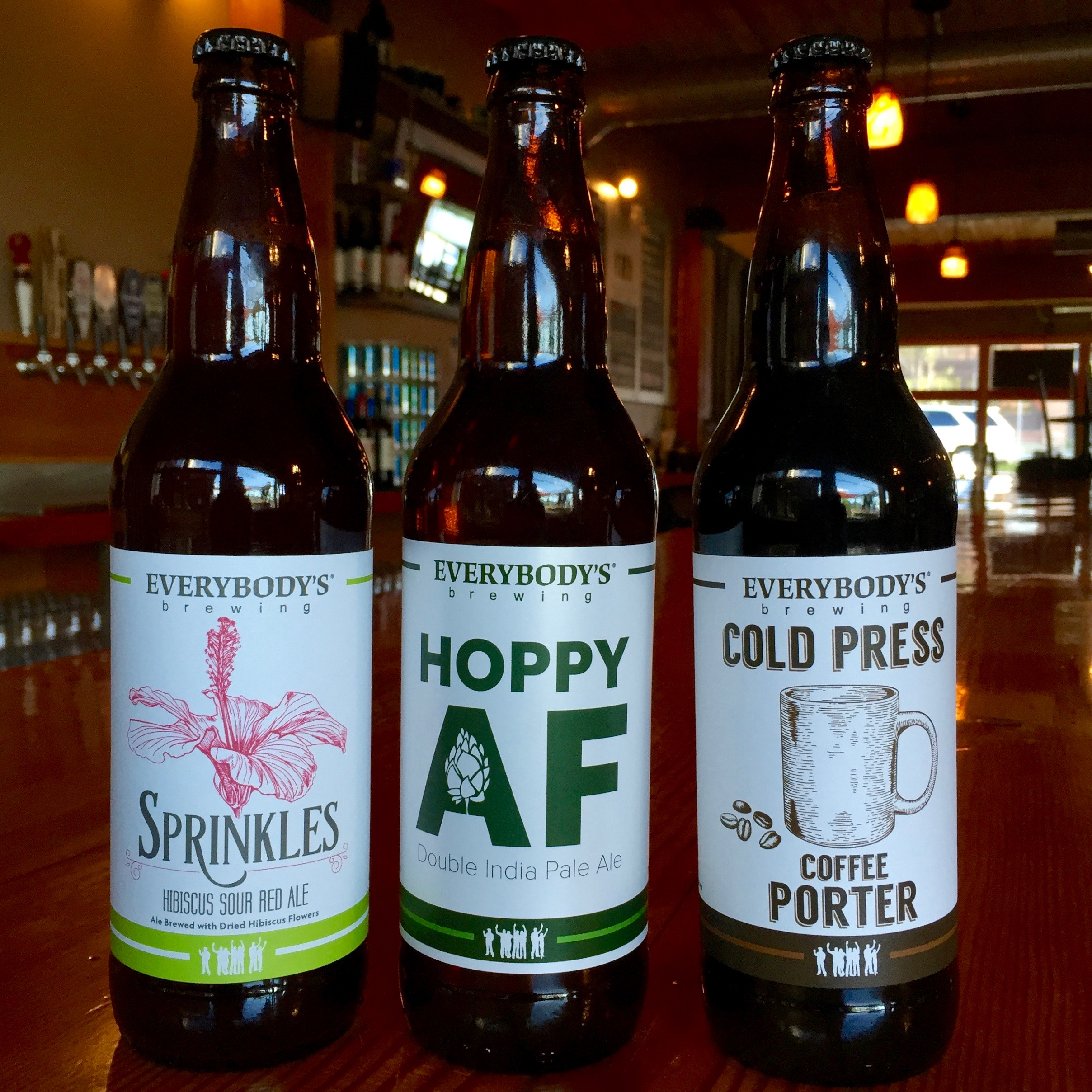 Everybody's Brewing bottles of its Sprinkles Hibiscus Sour Red Ale, Hoppy AF Double India Pale Ale, and Cold Press Coffee Porter. (image courtesy of Everybody's Brewing)