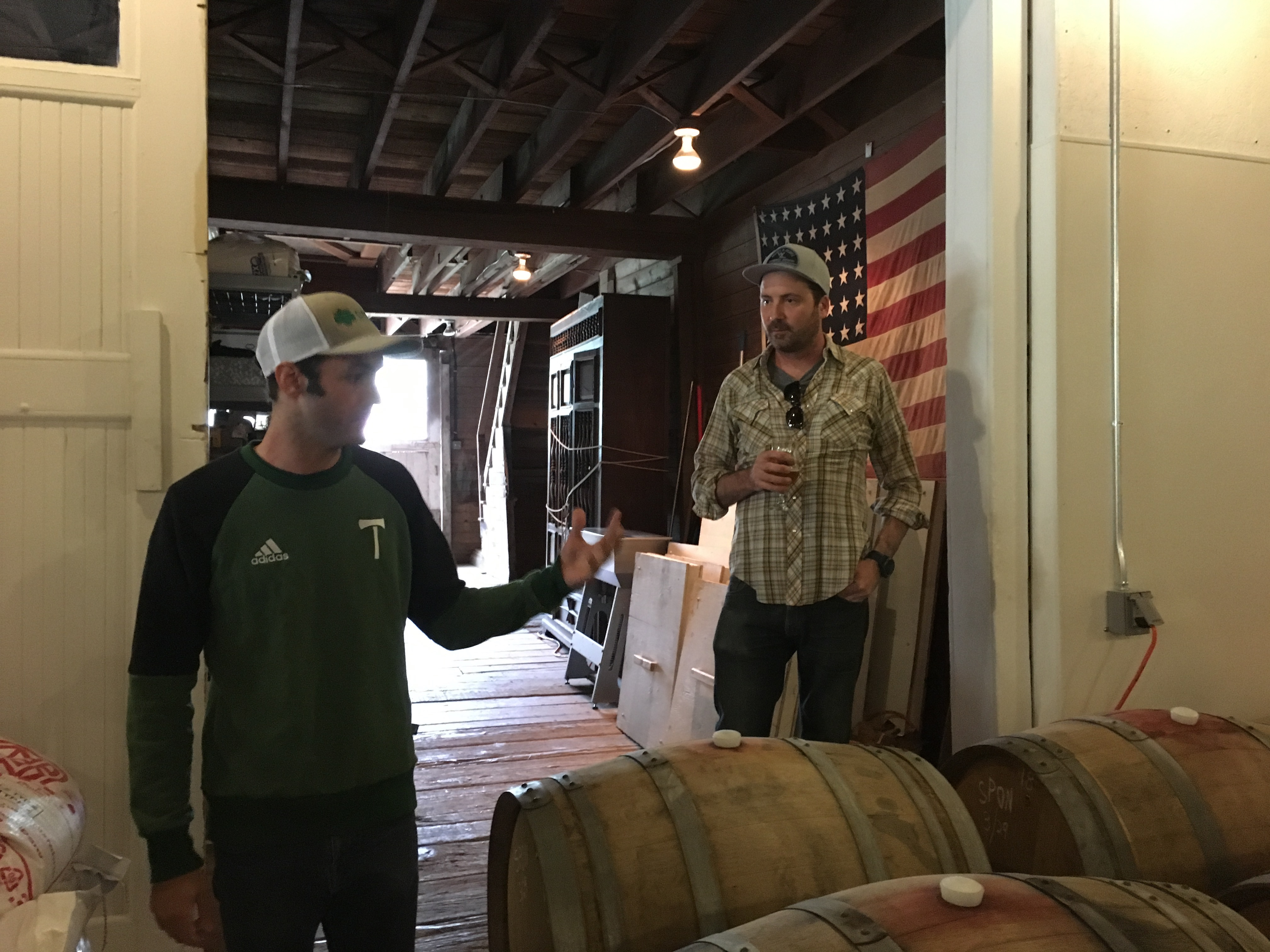 Jake Miller and Christian DeBenedetti discussing some beers aging in barrels with a 48 Star US Flag behind them.