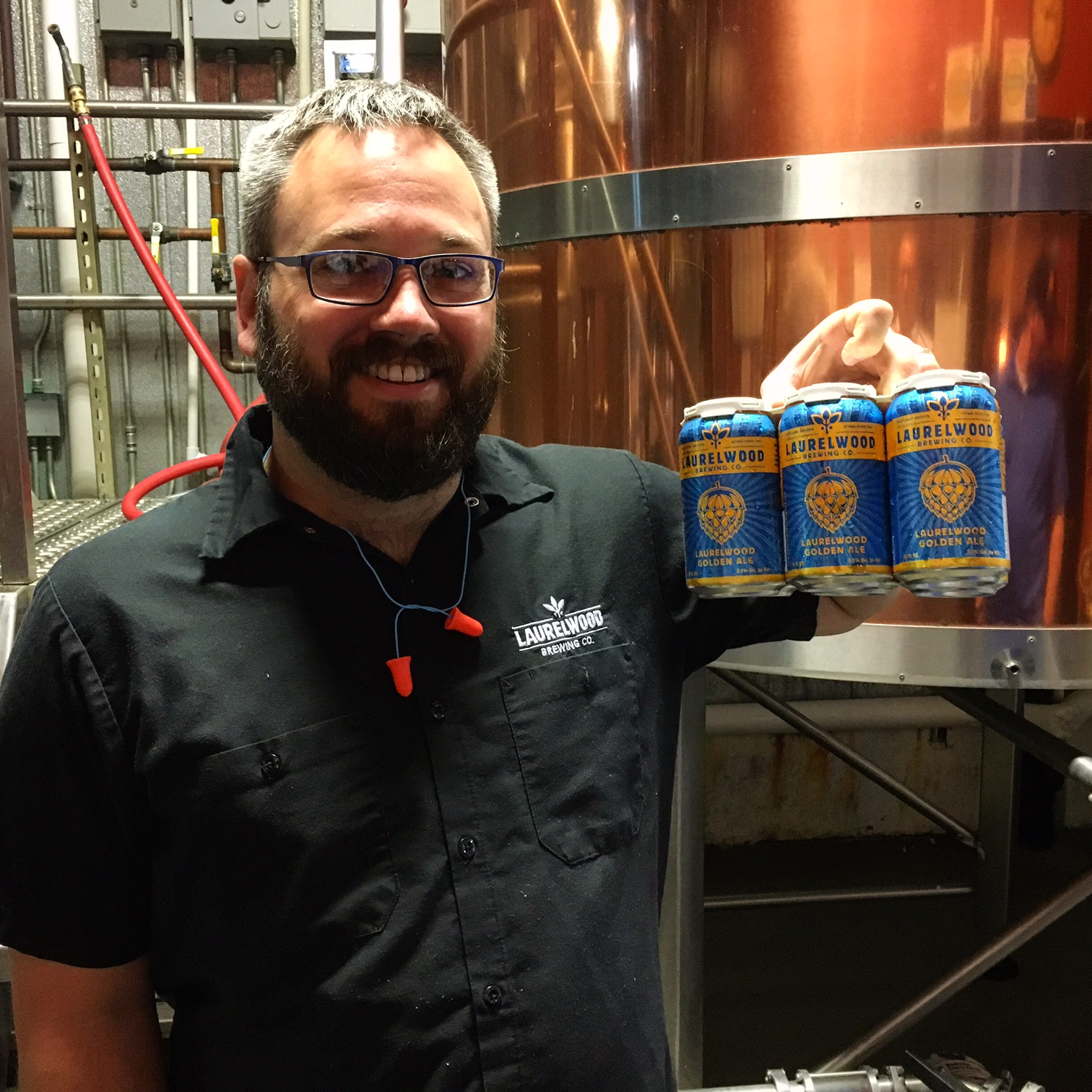 Laurelwood head brewer Shane Watterson holding a freshly canned six pack of Laurelwood Golden Ale.