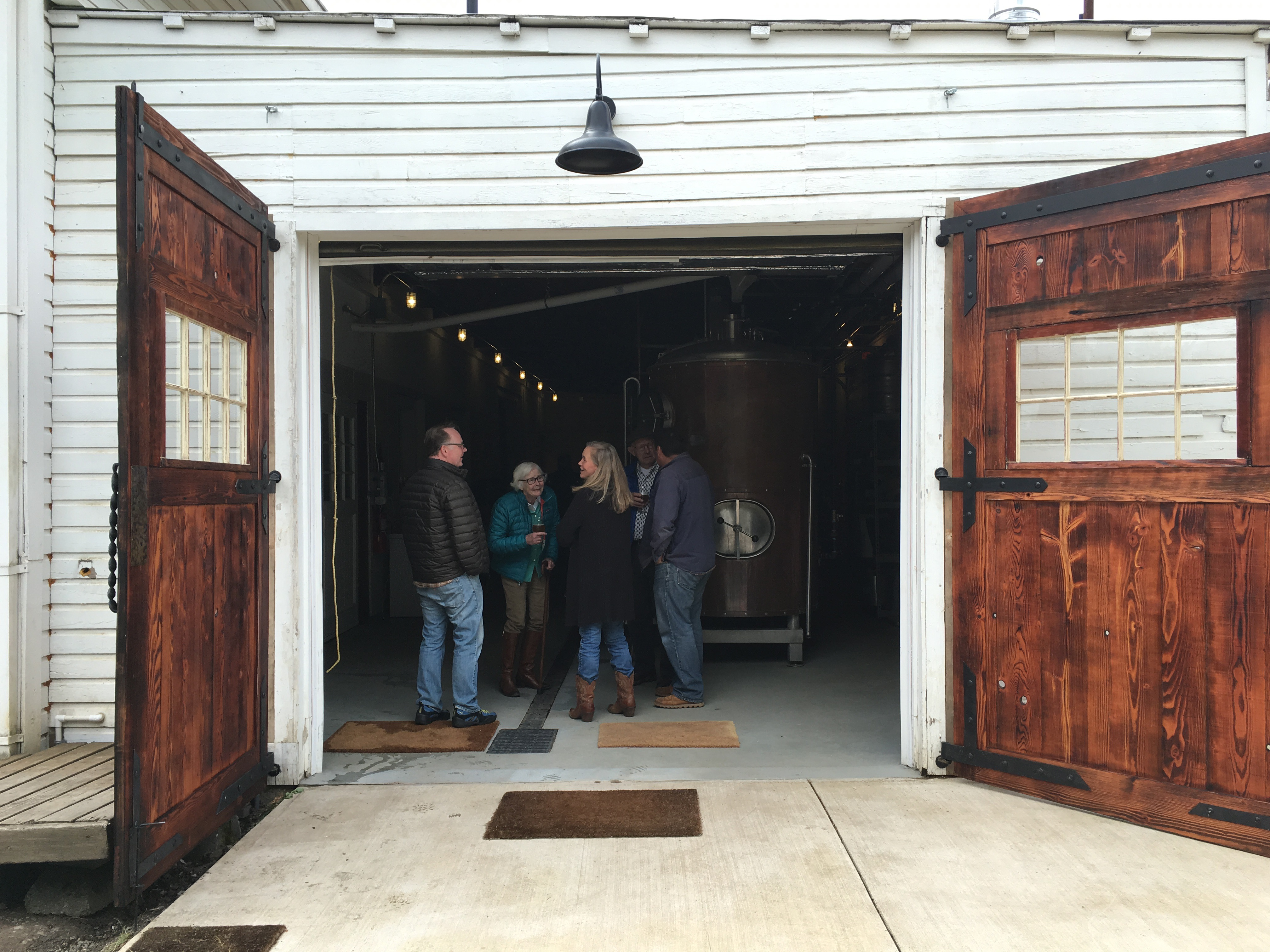 Magnificent brewery entry doors made from reclaimed wood from the Rainer Brewery that lead into Wolves & People Farmhouse Brewery.