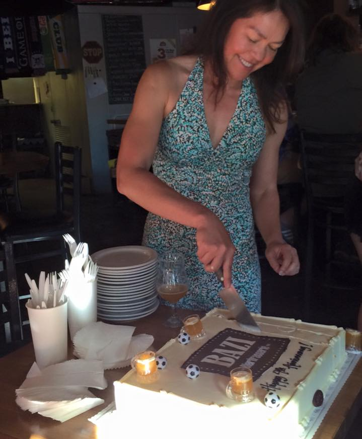 Proprietor Hilda Stevens cutting the Bazi Bierbrasserie 4th Anniversary Cake from 2015. (photo by Cat Stelzer)