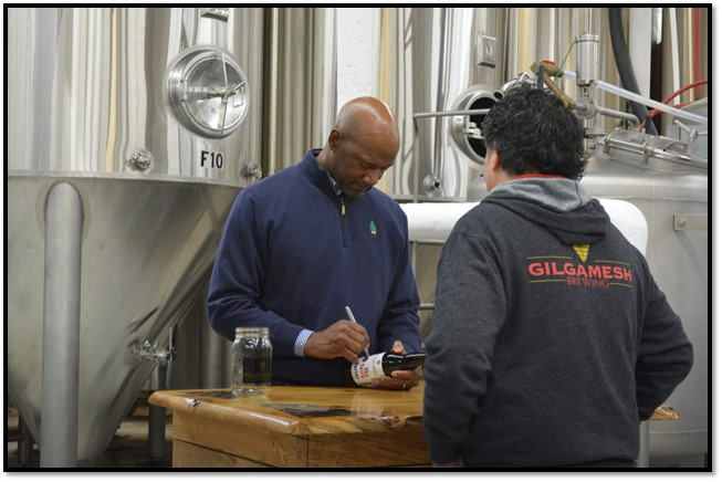 Terry Porter signing a bottle of Gilgamesh Brewing Terry Porter at the brewery. (image courtesy of Columbia Distributing)