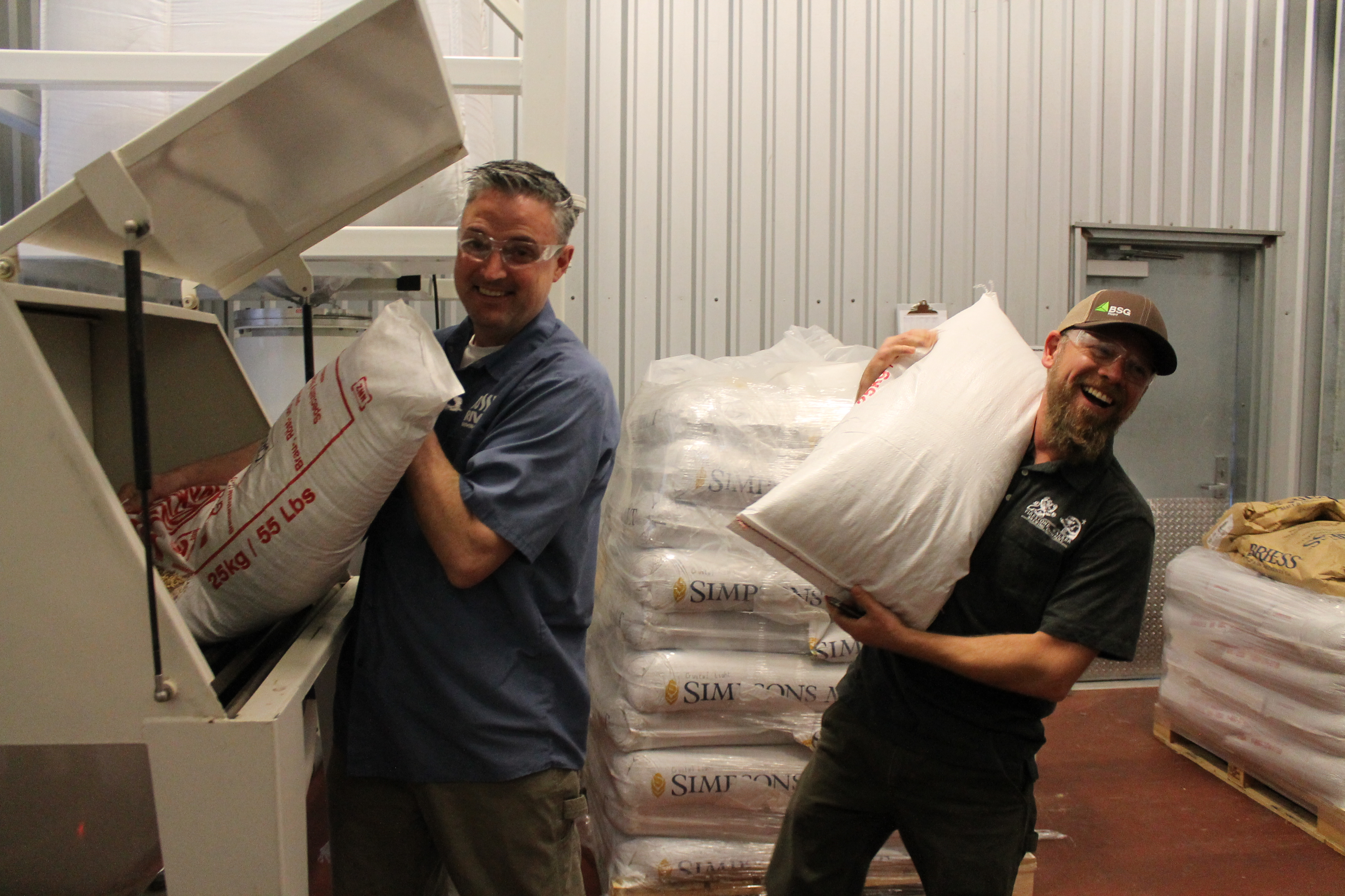 Vinnie and Matt hauling bags of malt. (image courtesy of Firestone Walker Brewing)