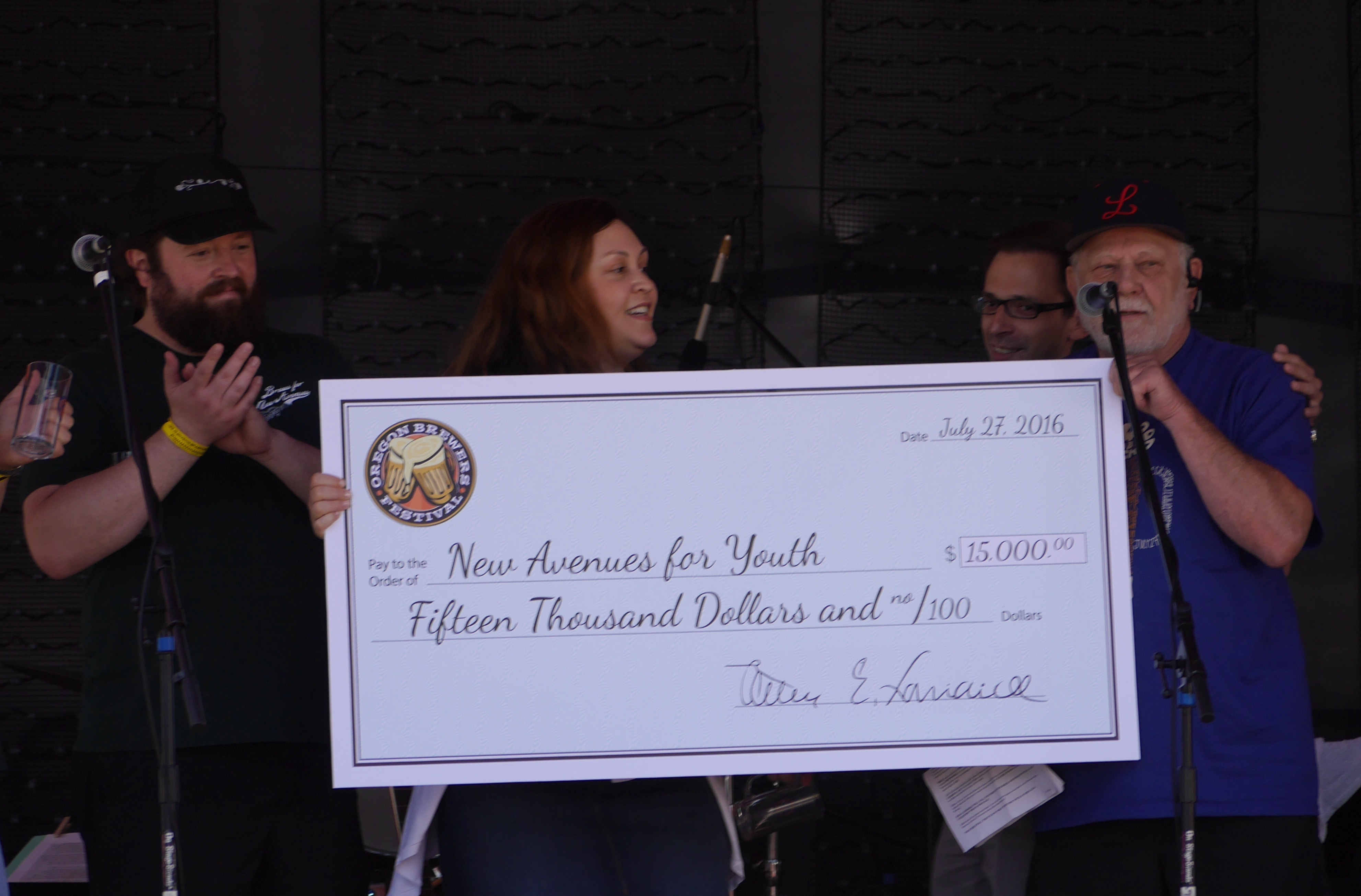 Oregon Brewers Festival founder Art Larrance presents a $15,000 check to New Avenues for Youth, the 2016 OBF beneficiary. (photo by Cat Stelzer)