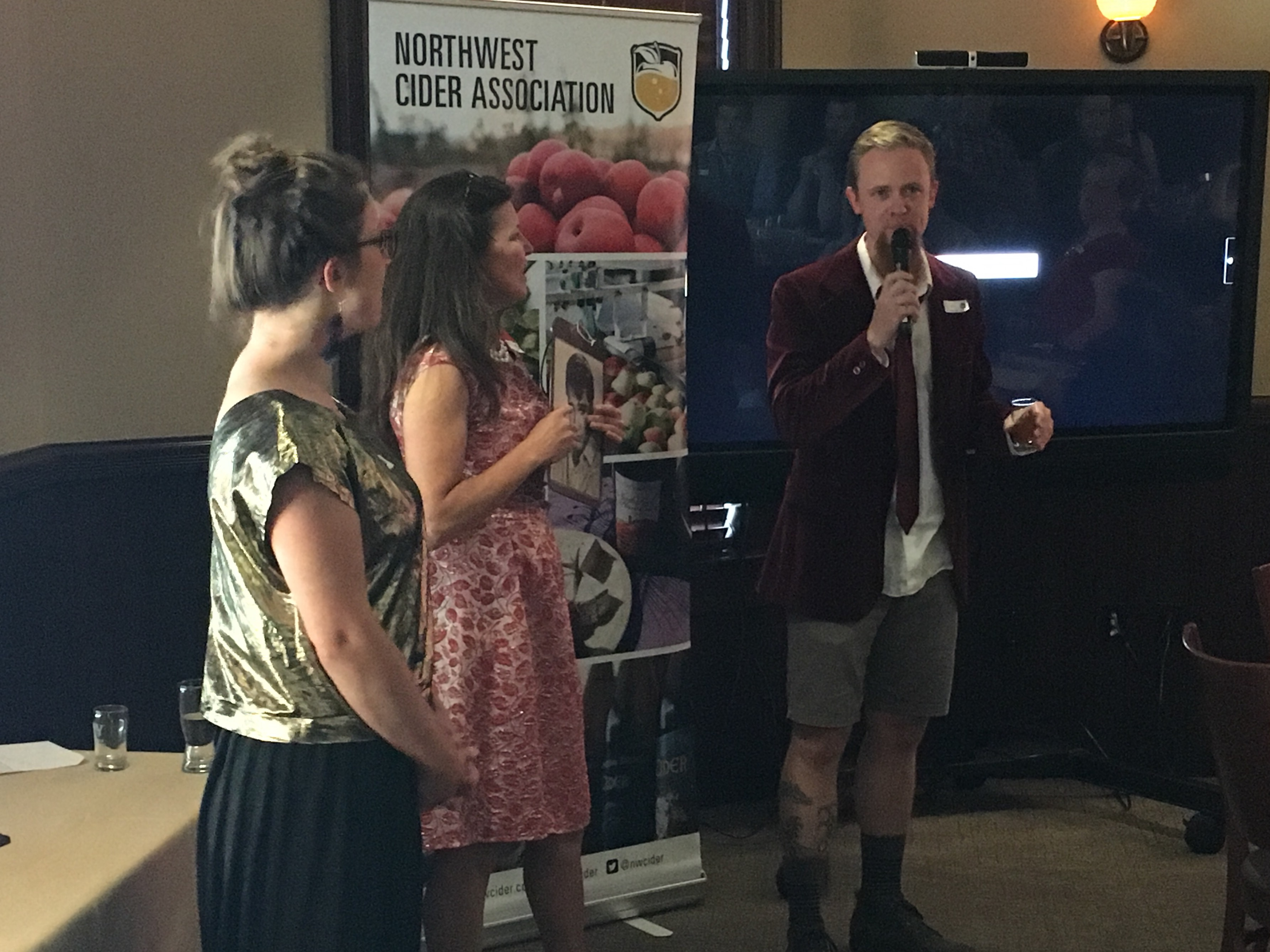 Rev. Nat talking during the Portland International Cider Cup Awards while NW Cider Executive Director Emily Ritchie (left) and Carolyn Winkler (center) look on.