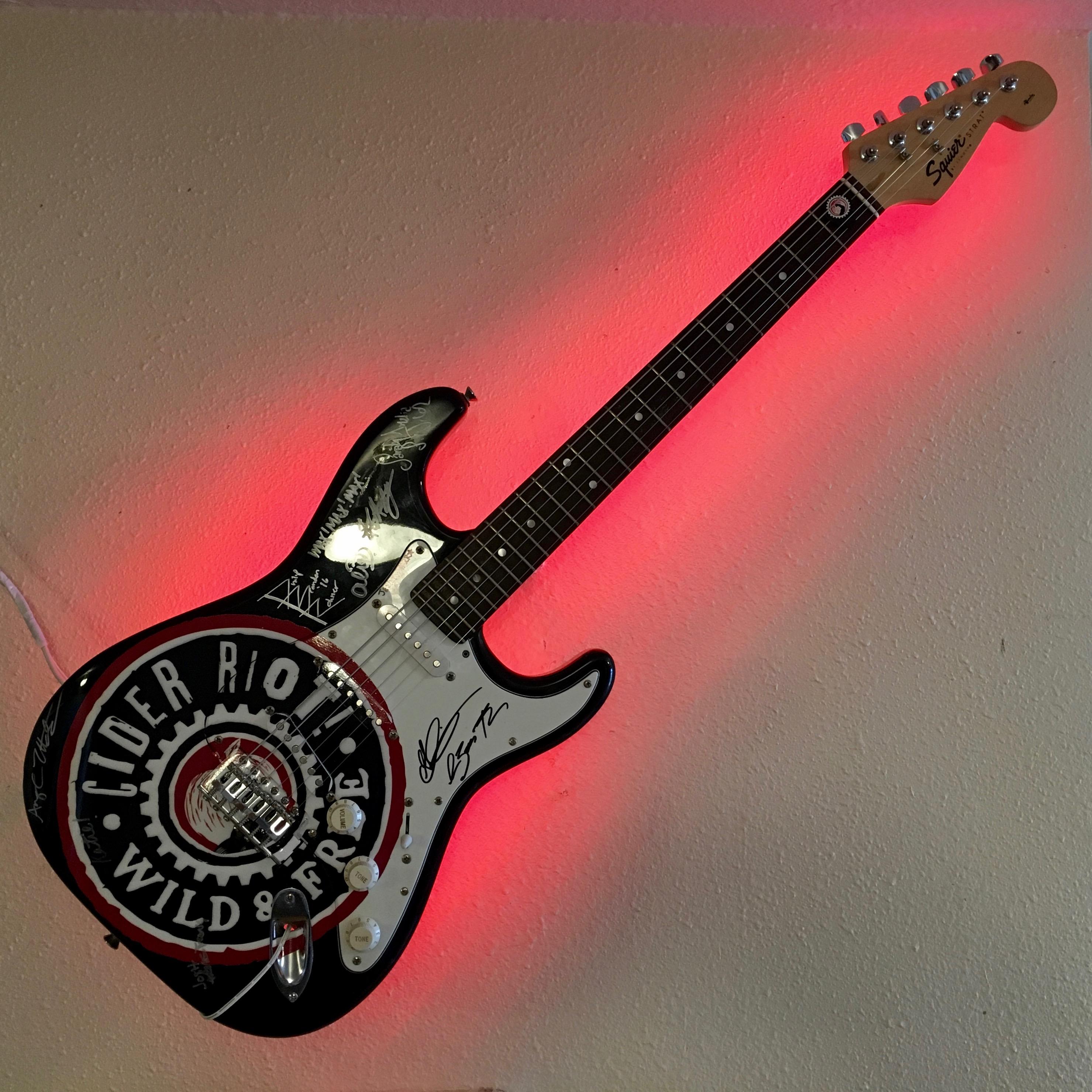 A Cider Riot! guitar adorns the walls at Cider Riot! Pub.