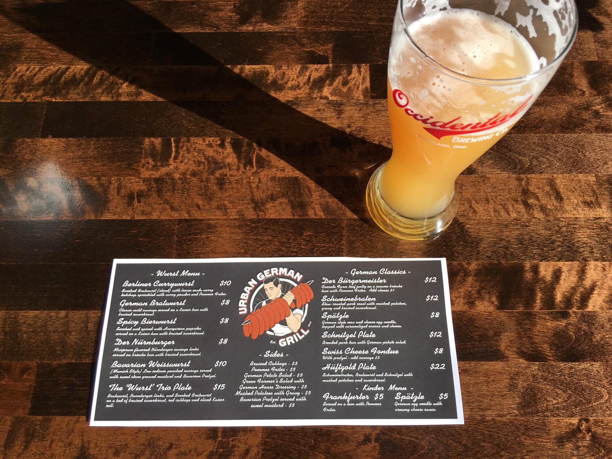 A Hefeweizen and the food menu at Occidental Wursthaus. (photo by Cat Stelzer)