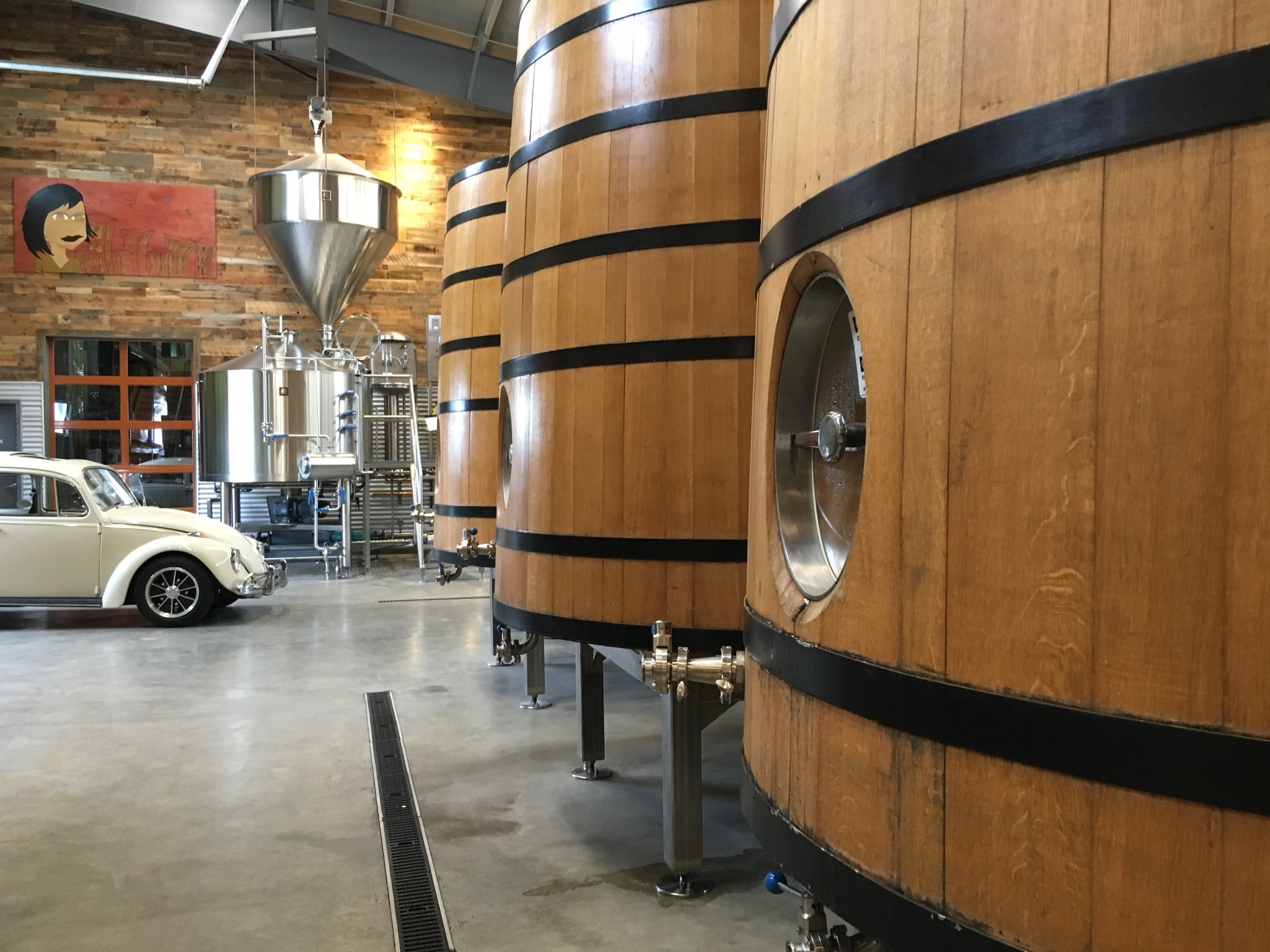 A Volkswagen Beetle in the background of a some of the foeders at Anchorage Brewing. (photo by Cat Stelzer)