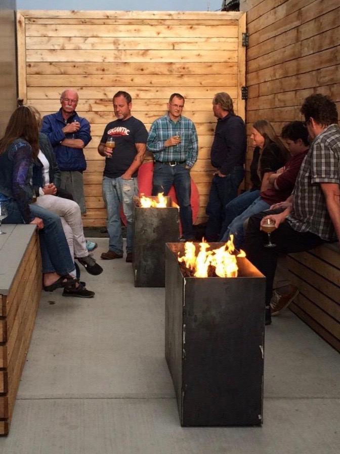 Brewers gather around the firepit at Anchorage Brewing, including Anchorage Brewing owner:brewer Gabe Fletcher wearing a Gigantic Brewing shirt. (photo by Cat Stelzer)