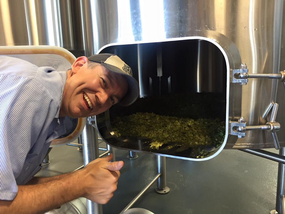 Bolt Minister of 54-40 Brewing looking at the Amarillo hops in the hop back while he brewed a collaboration Red IPA with Wayfinder Beer. (image courtesy of Wayfinder Beer)