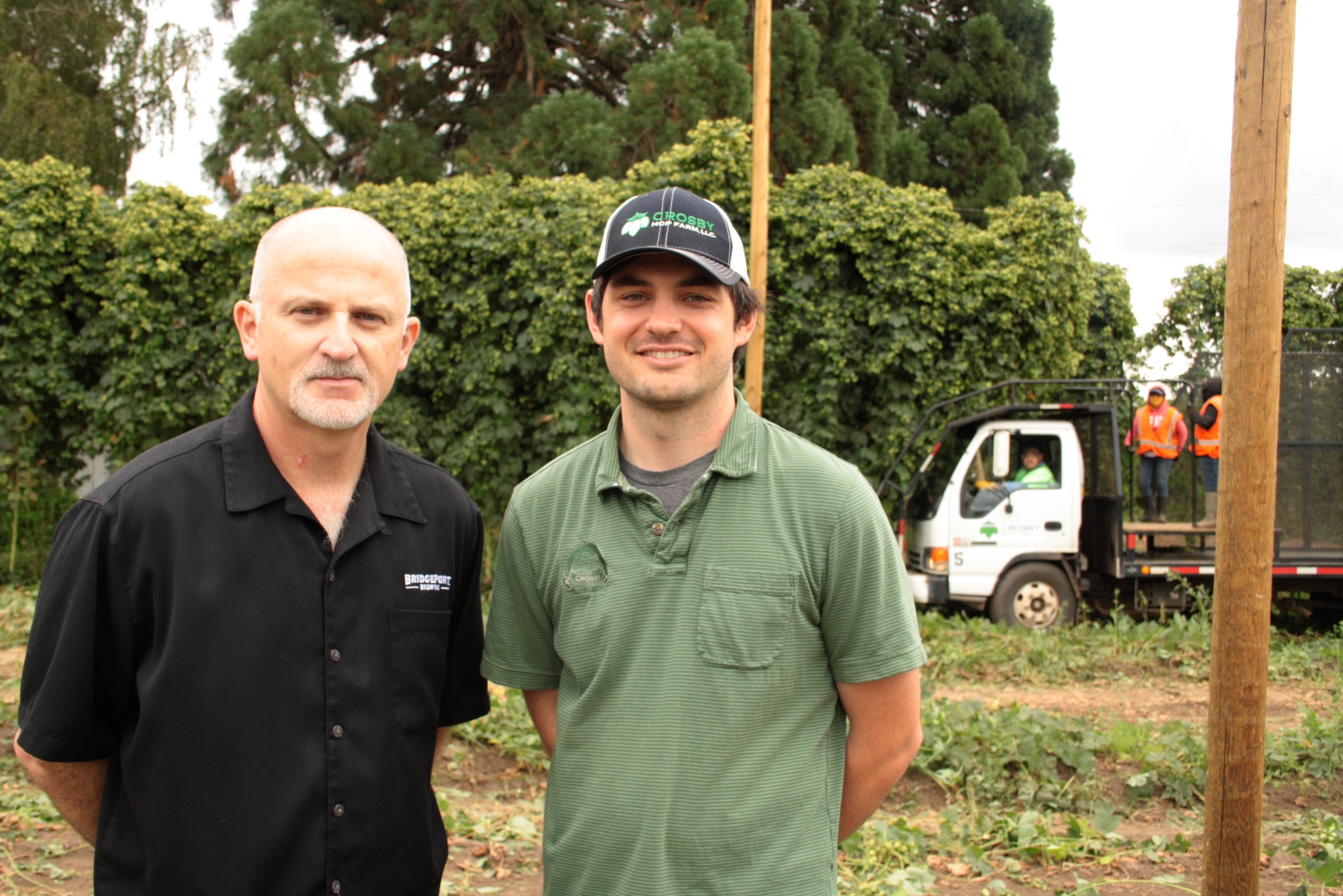Jeff Edgerton of BridgePort Brewing and Blake Crosby of Crosby Hop Farm during the 2016 hop harvest. (photo by Ryan Spencer)