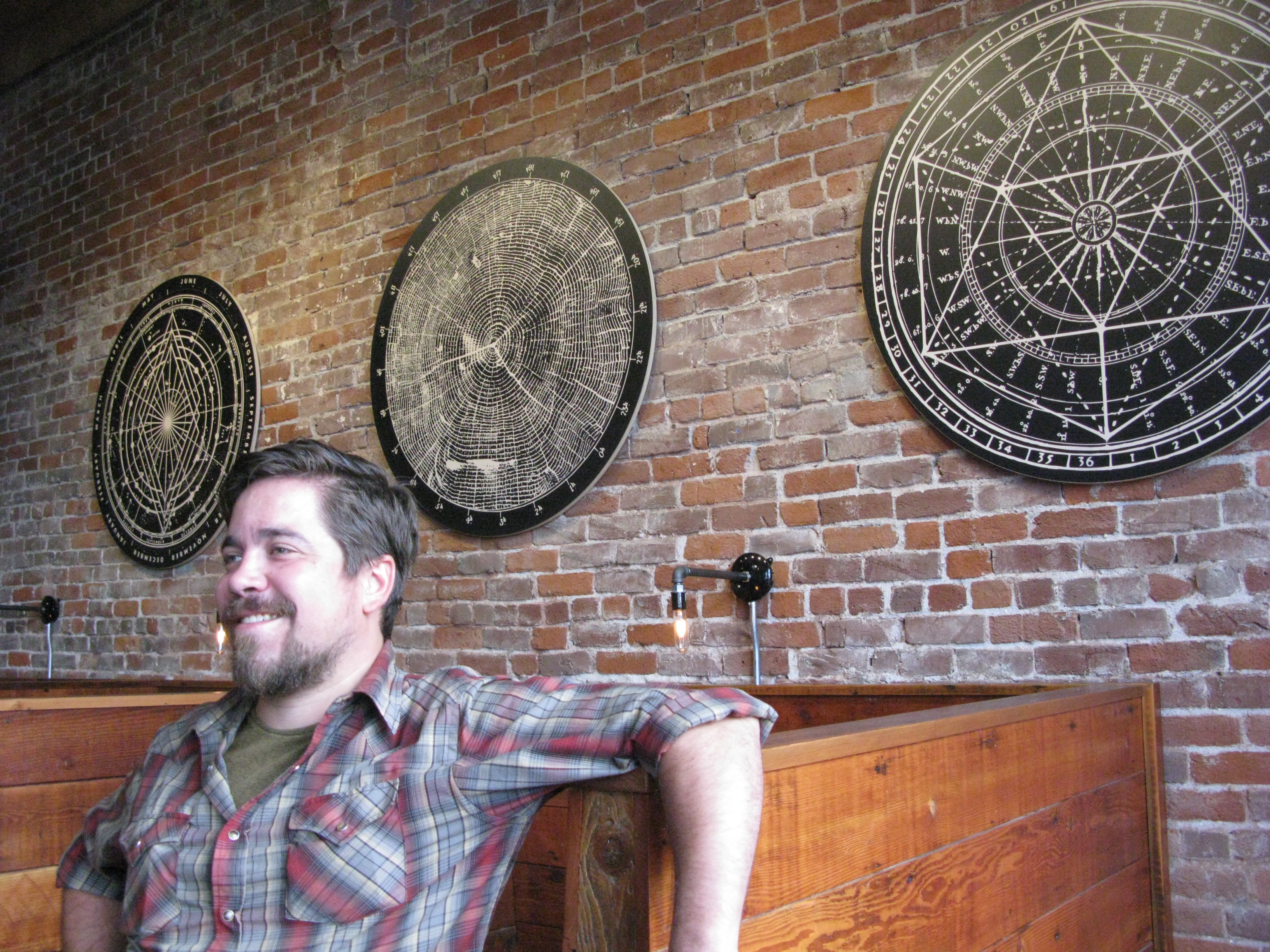 Jonathan Carmean in front of the south wall which features -- as do the the beer mats -- three more of Landaus geometric pieces. (FoystonFoto)