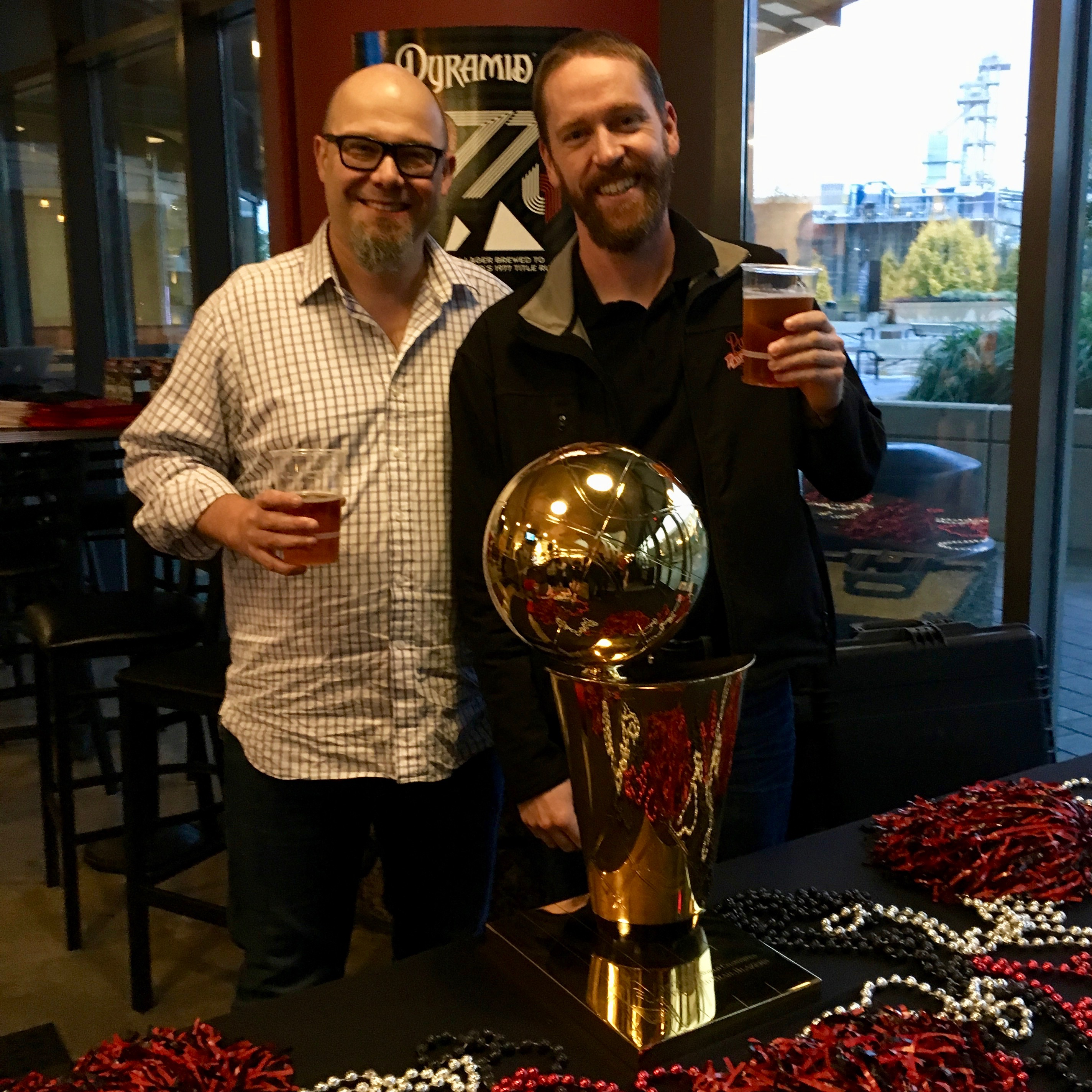 Robert Rentsch and Ryan Pappe of Pyramid Brewing posing in front of the 1977 Portland Trail Blazer NBA Championship Trophy.