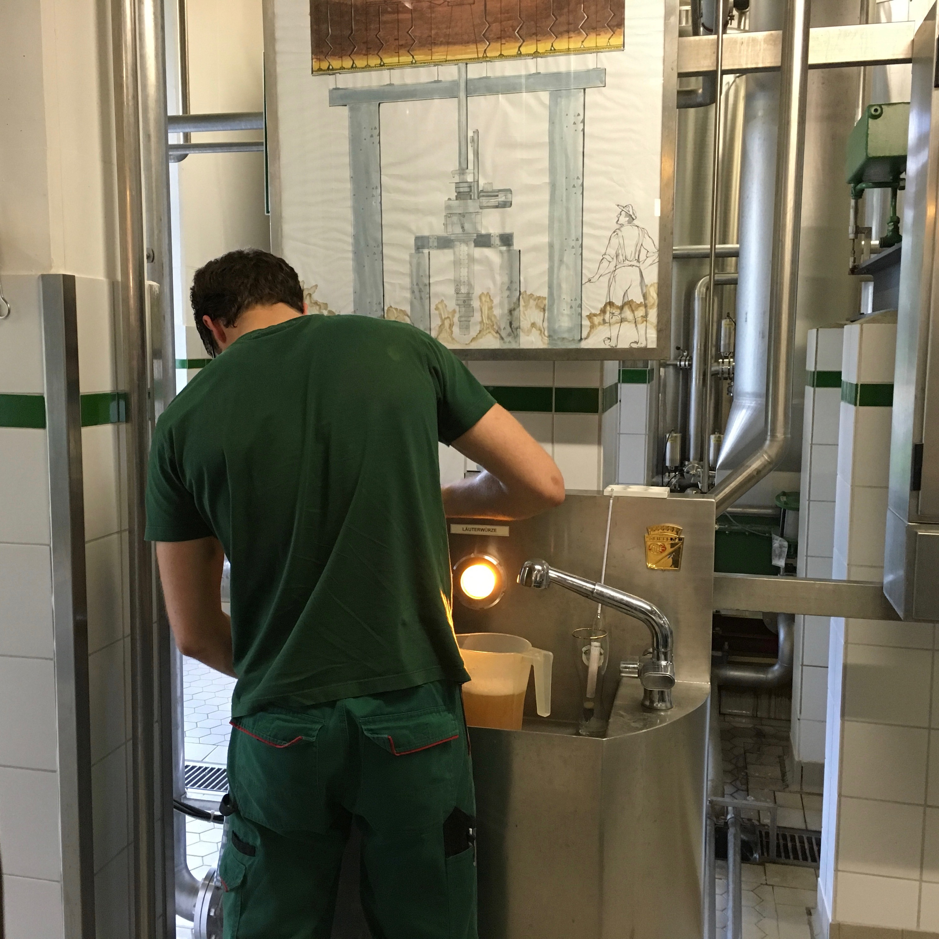 "An Ayinger brewer in his ""work greens"" inside the brewery."