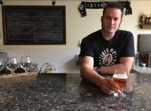 Abram Goldman-Armstrong, founder and owner of Cider Riot! behind the bar at the Cider Riot! Pub.