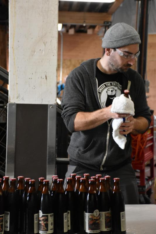 Lead Brewer Austen Conn on the Love, Lost At Sea bottling line. (image courtesy of Buoy Beer)