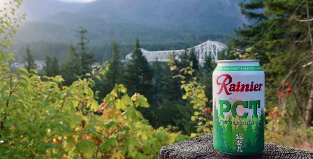 A can of Rainier PCT Session IPA with the famous Bridge of the Gods in the background.
