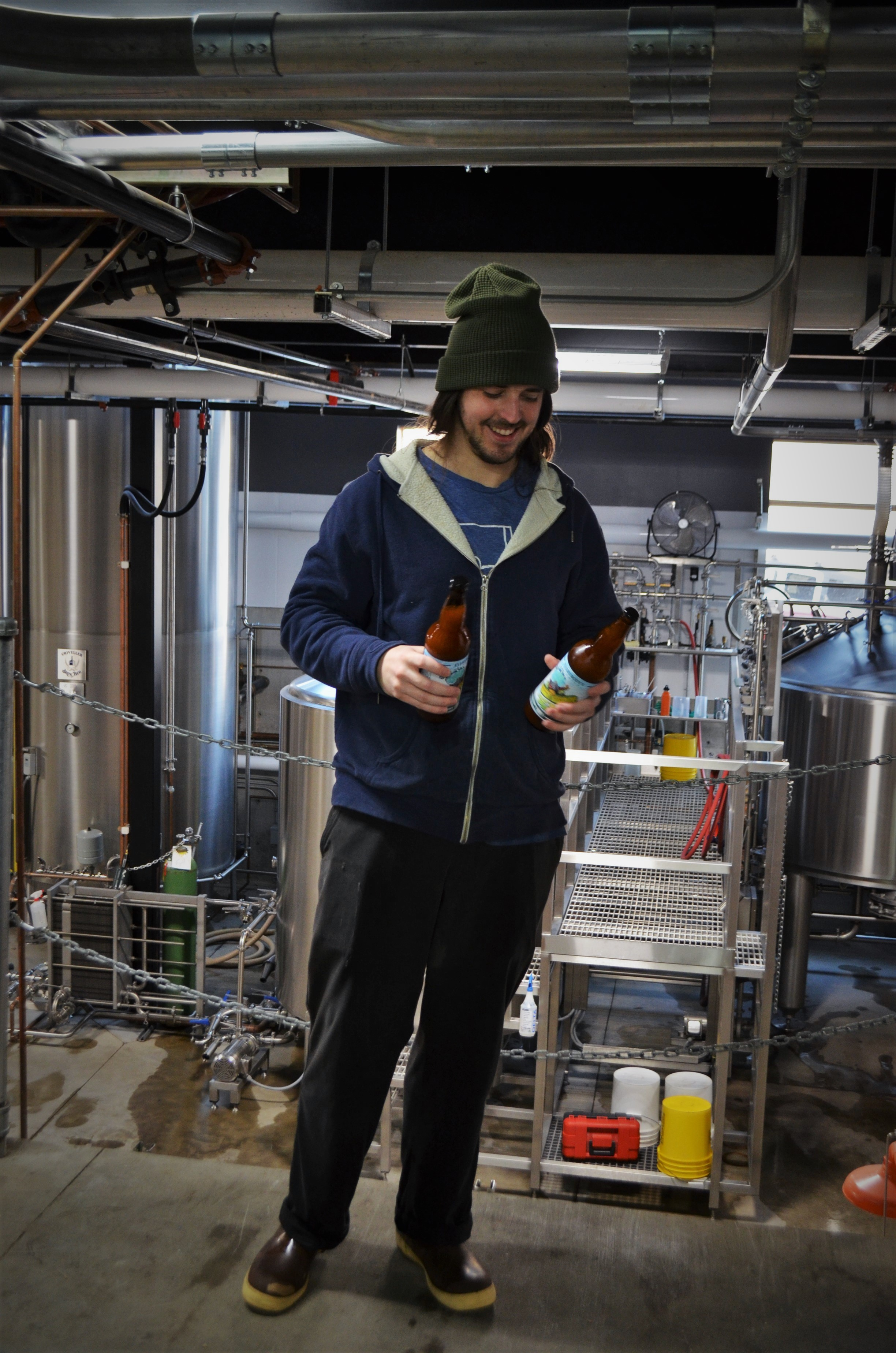 image of Sam Mertz, a brewer at Everybody's Brewing inspecting a bottle of Foggy Goggles Hazy IPA courtesy of Everybody's Brewing