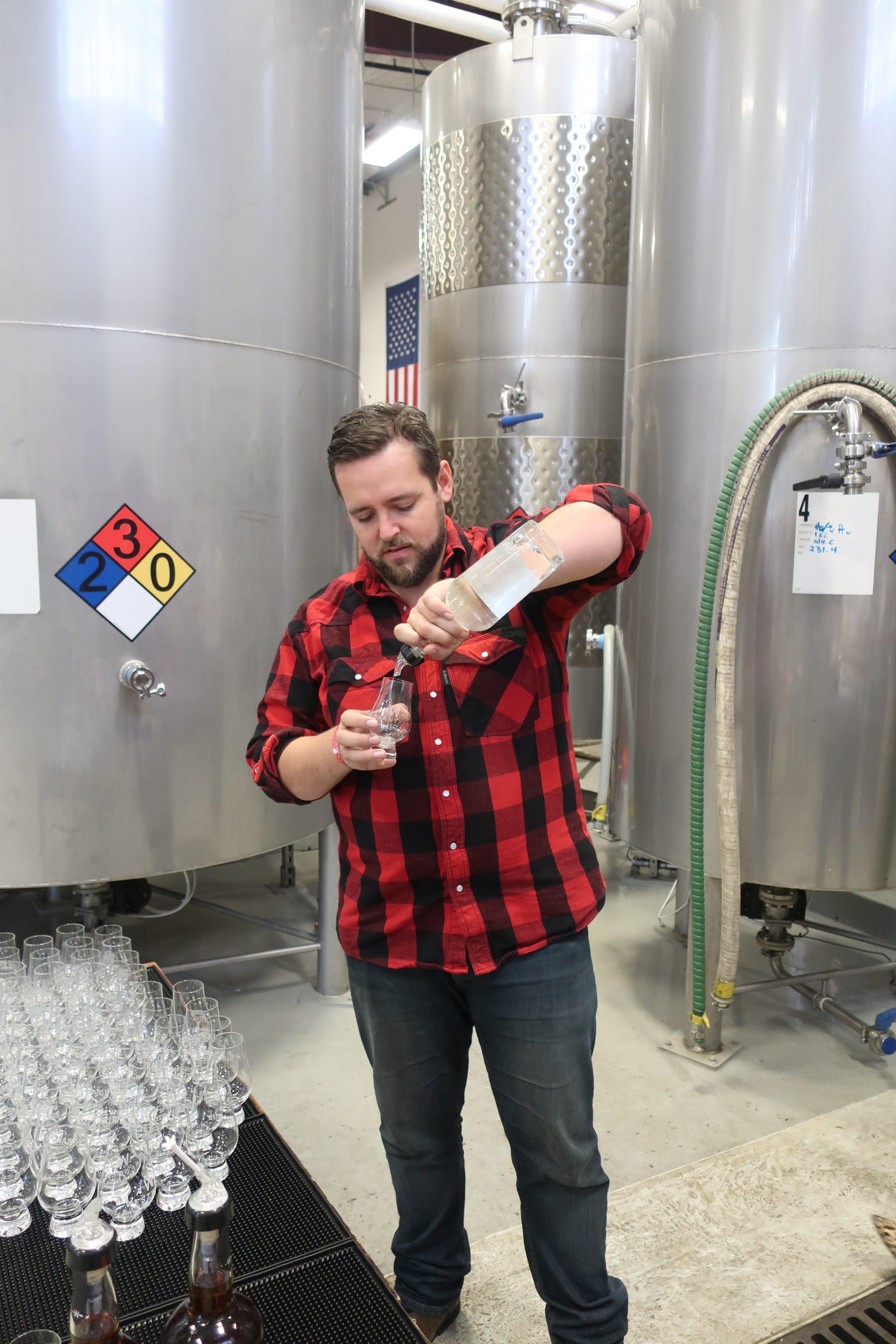 Jordan Felix pouring unaged white dog whiskey at Westward Whiskey.