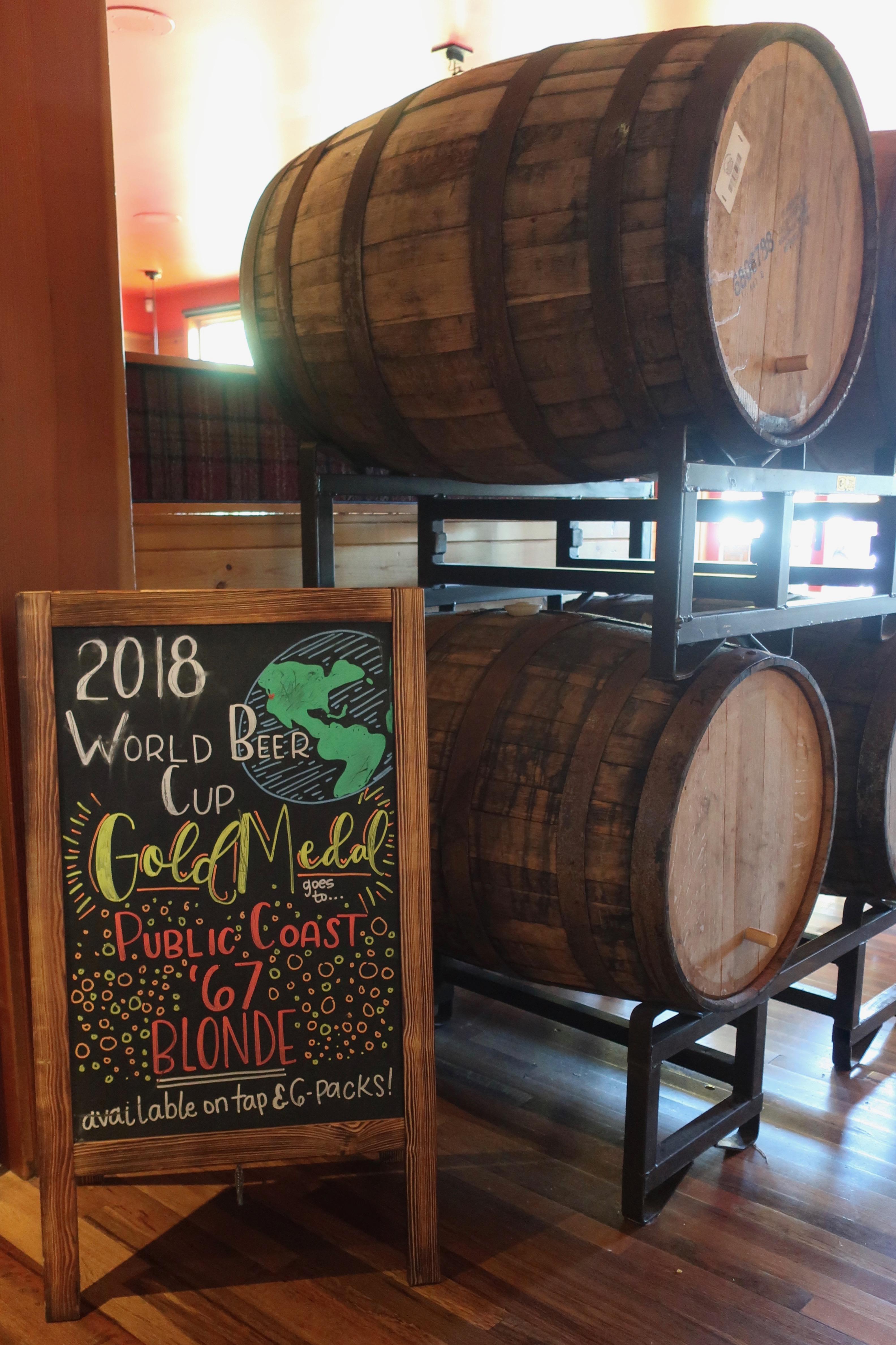 Barrels aging inside Public Coast Brewing.