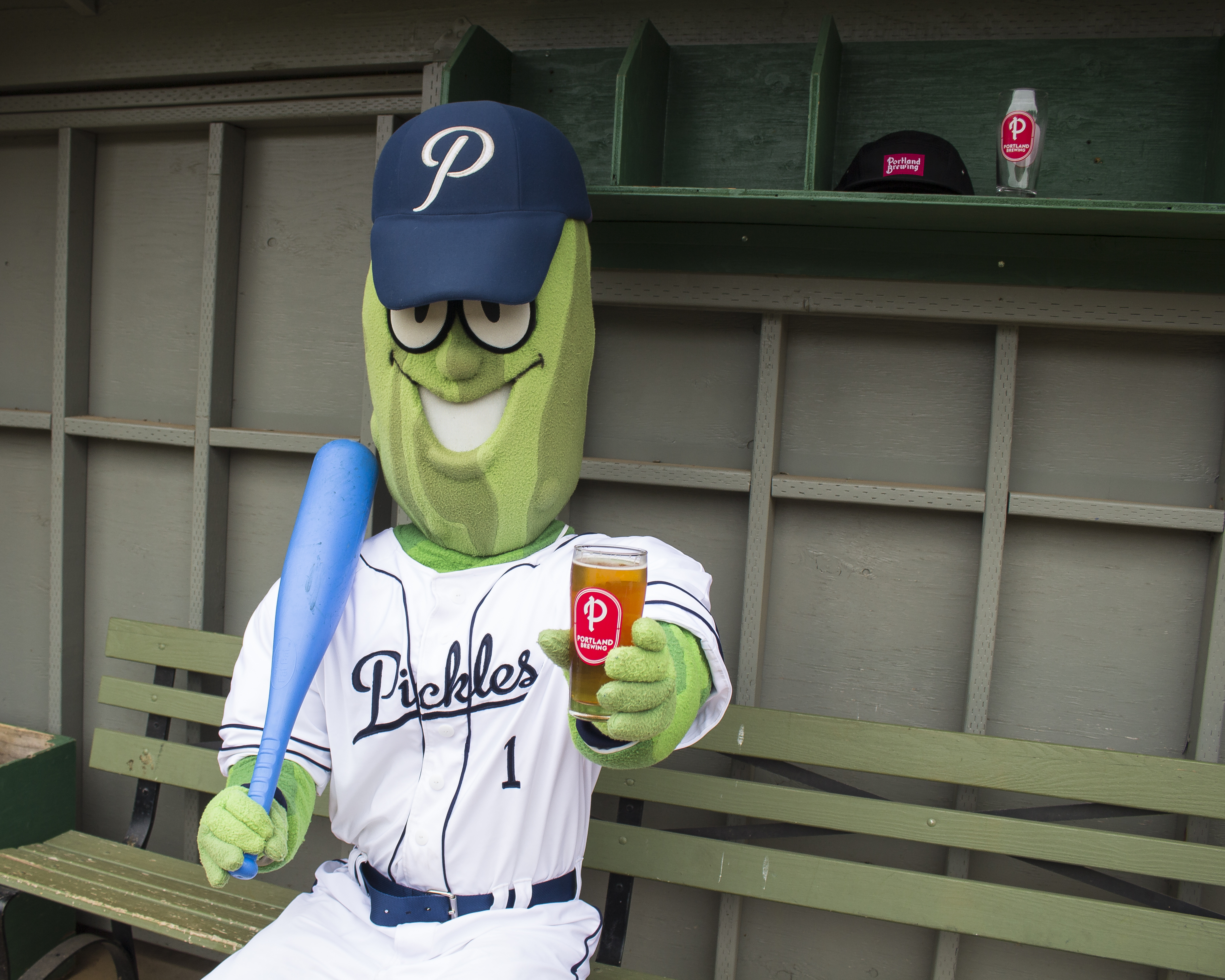 Dillon The Pickle in the dugout with a Dill's Pils. (image courtesy of Portland Brewing)