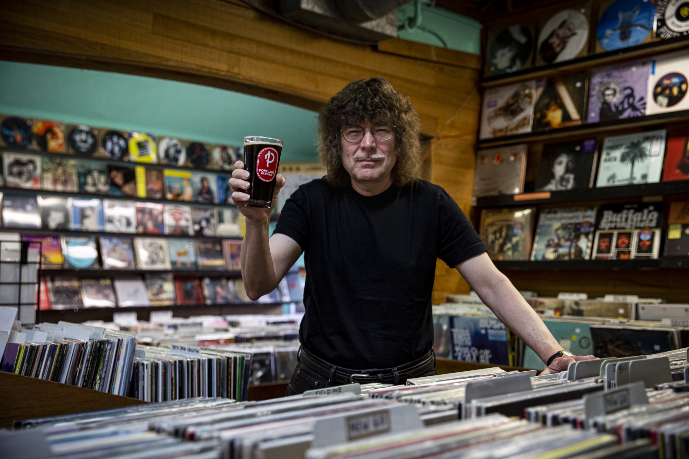 Terry Currier, owner of Music Millennium behind a lot of vinyl records with a Portland Brewing In The Groove Black Vinyl Lager. (image courtesy of Portland Brewing Co.)
